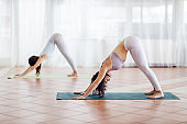 Two fit attractive yogi girls in Downward-Facing Dog yoga pose. Yoga studio interior.