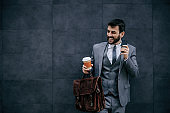 Young smiling fashionable businessman leaning on the wall and holding smart phone.