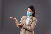 Young businesswoman in formal wear with protective face mask standing and gesturing with hands like she is showing something.