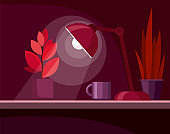 Workplace with plant and lamp on the table. Dark red background. Night office room.