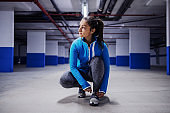 Young fit attractive caucasian sportswoman in tracksuit running fast in garage. Urban life concept.