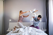 Young playful couple having pillow fight in the morning in bedroom.