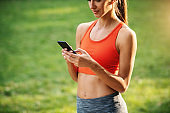 Young attractive slim sportswoman taking a break after running and using smart phone for texting messages on social media.sportswoman, girl, woman, female, fit, slim, sportswear, nature, sports, exercises, people, real people