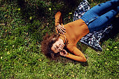 Top view of mixed race woman lying down on the lawn, enjoying music on a beautiful sunny day.