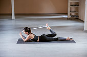 Side view of brunette lying down on the mat and stretching her leg with rope.