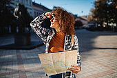 Young attractive female tourist holding map and looking around while standing on square.