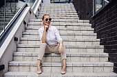 Beautiful smiling fashionable businesswoman sitting on the stairs in front of business center and posing.