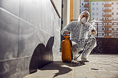Cleaning and Disinfection outside around buildings, the coronavirus epidemic. Professional teams for disinfection efforts. Infection prevention and control of epidemic. Protective suit and mask. Professional specialist full protective cleaning outside.