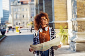 Young gorgeous mixed race female tourist holding map and admiring an old building in new town.
