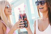 Happy women friends enjoying cold drinks at sunny beach