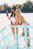 Stylish summer girls posing at lifeguard tower