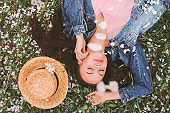 Top view serene carefree hipster woman laying on grass on summer garden
