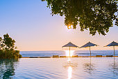 Beautiful tropical outdoor beach sea ocean with umbrella and chiar around outdoor swimming pool at sunset or sunrise time