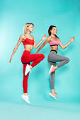 Time for sport. Two young and attractive sporty girls in sportswear jumping in studio against blue background. Sport and fitness. Studio shot