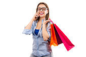 Happy woman with shopping bags having call