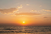Colorful sunset on a sandy beach, waves with foam on the sand. Ocean, coast. Soft selective focus.