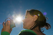 Woman Holding a Cup of Coffee Against Sunlight