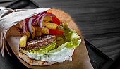 greek meat gyros with tzatziki sauce, vegetables, feta cheese and french fries
