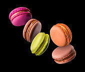 Flying french colorful macaroons on wooden table isolated on black
