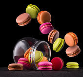 Flying french colorful macaroons and jar on wooden table isolated on black