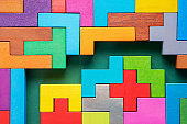 Colorful maze on green background. Labyrinth of colorful wooden blocks, top view, flat lay.