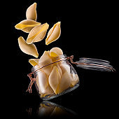 Jar of conchiglie pasta shell on wooden table isolated on black background