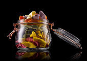 Jar of colorful farfalle pasta on wooden table isolated on black background