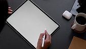 Overhead shot of a woman drawing on mock up tablet on black table background