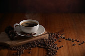 Close up view of a cup of hot coffee on wooden tray decorated with coffee beans