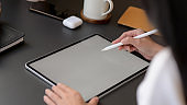 Cropped shot of a woman drawing on mock up tablet on black table background