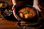Female hands holding a bowl of chicken Massaman Curry soup to serve