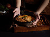 Female hand holding a bowl of chicken Massaman Curry, Thai food
