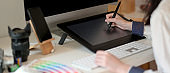 Graphic designer working on drawing tablet with stylus pen, computer and supplies on white office desk