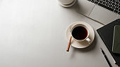 White table with coffee cup, laptop, stationery and copy space in office room