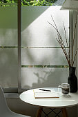 Cropped shot of modern home interior design with flower vase and diary notebook