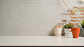 White table with copy space, pencils, mug and plant pots inn home office room