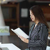 Female office worker reading her schedule book while sitting in office room
