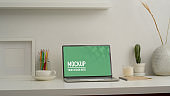 Home office desk with mock up laptop, stationery and decorations