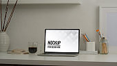 Mock up laptop on white table with supplies, stationery and decorations in home office room