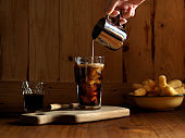 Hand pouring milk into ice coffee on wooden table with deep fried dough sticks