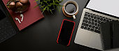 Stylish workspace with smartphone, laptop, schedule book, coffee cup and decoration