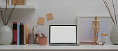 Designer home office with mock up laptop, painting tools, books and decorations on white table