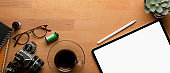 Rustic worktable with mock-up tablet, coffee cup, camera, schedule books, supplies and copy space