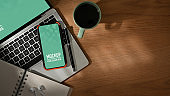 Wooden table with smartphone, laptop, coffee cup, stationery and copy space
