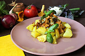 Fried potatoes with chanterelles on a plate and greens
