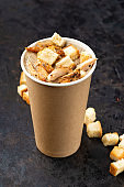 French cuisine hot food delivery - Close-up of mushroom soup with chicken meat in disposable paper cups on a dark stone surface. Healthy food concept