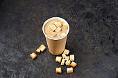 French cuisine hot food delivery - Close-up of mushroom soup in disposable paper cups on a dark stone surface.