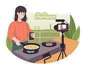 Female chef cooking in the kitchen while recording video using her camera for her online video channel. Food blogger preparing some food