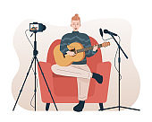 Man singing and playing acoustic guitar while recording video using camera and microphone. Male singer doing cover song for his online video channel