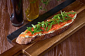 Bread toast with salted salmon, pesto sauce and cream cheese ricotta. Gourmet snack. selective focus